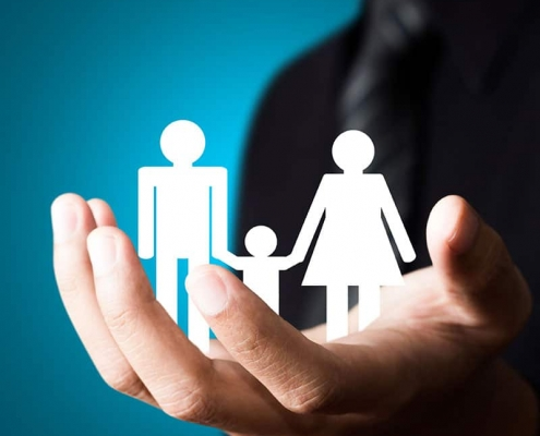 Larger Life Insurance paper cutout of a family in palm of hand.