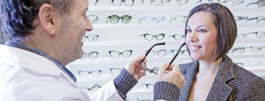 Man helping a woman to try on eyeglass frames.