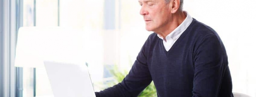 Older man with laptop at a table.