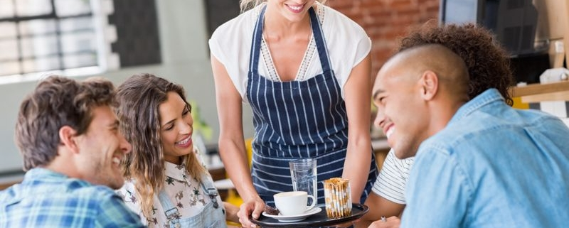Waitress serving young patrons food in a restaurant.