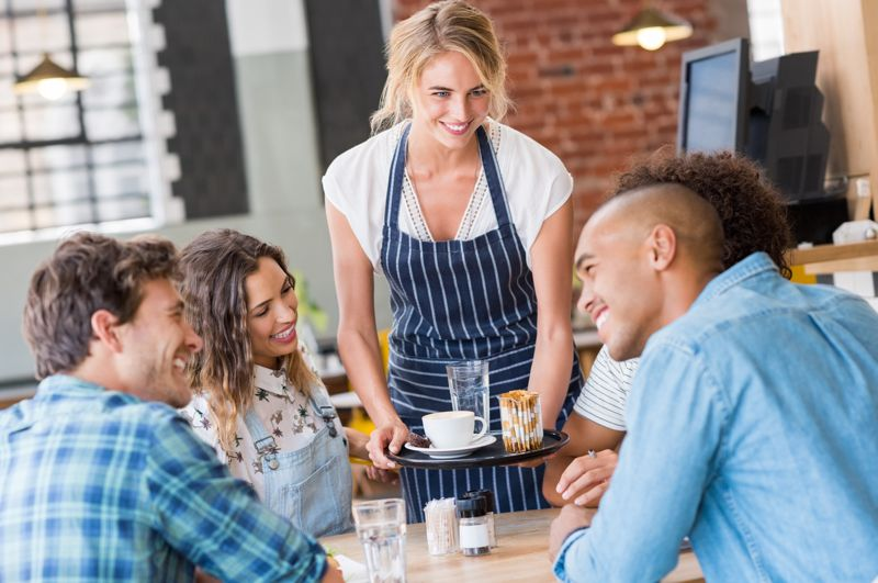 waitress serving patrons food in restaurant