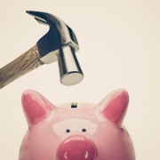 Hammer about to break a piggy bank.