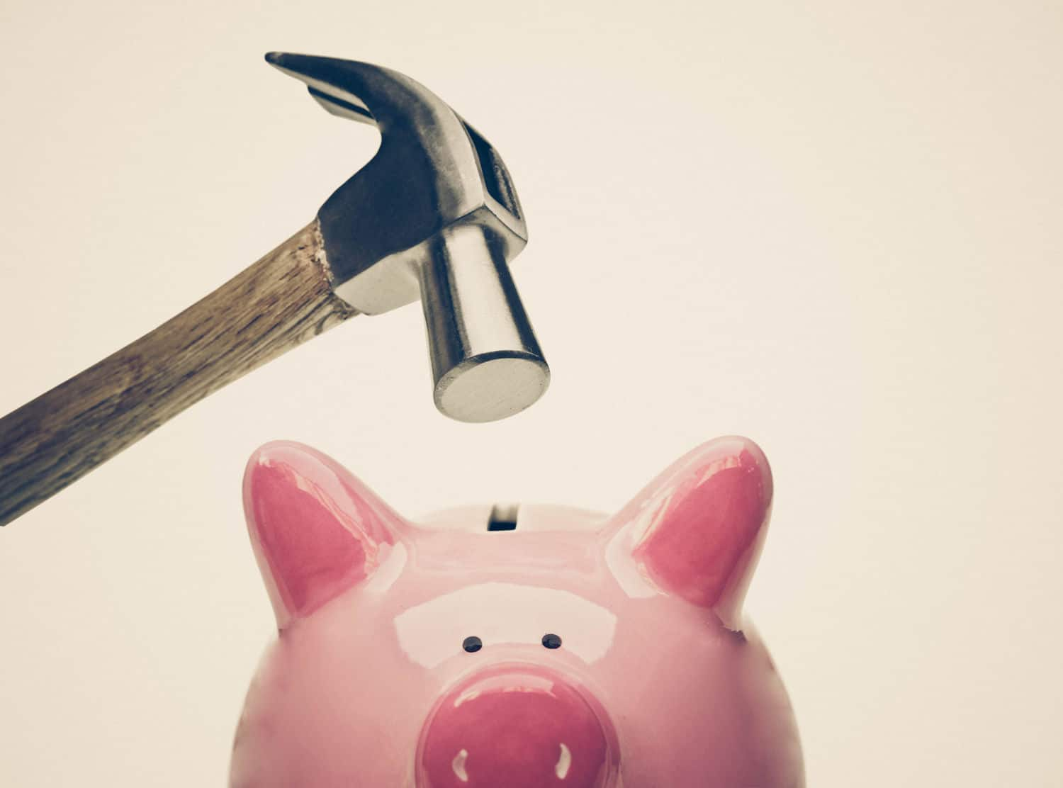 Hammer about to break a piggy bank - Benefit Strategies Inc