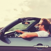 Young couple driving in a convertible.