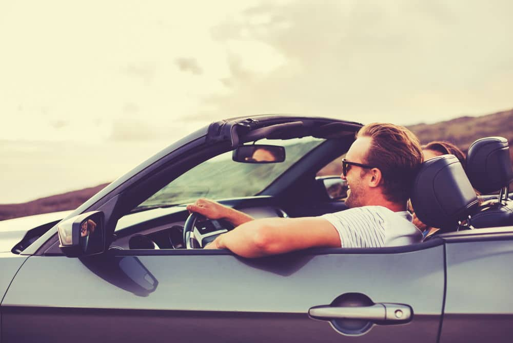 Young couple driving in a convertible - Benefit Strategies Inc