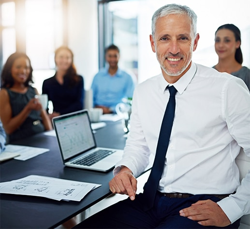 Older man at a desk with computer and young staff in the background