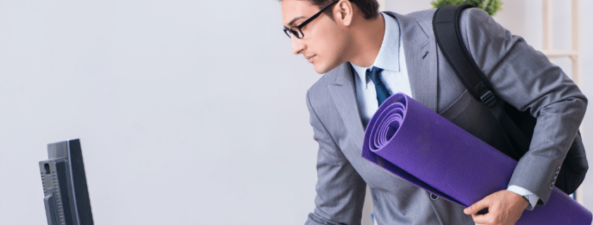 Young businessman standing at computer with Yoga mat under his arm