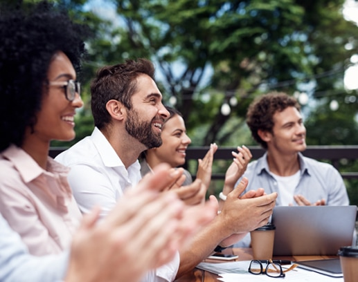 4 young business people sitting outdoors and clapping