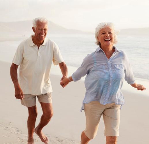 Older couple running barefoot on a sandy beach